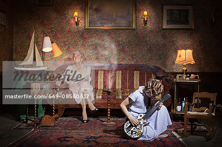 Girl playing guitar at grandmother's Stock Photo - Premium Royalty-Free, Image code: 649-08560617