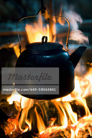 A kettle boils on top of a fire in a lavvu, a temporary home and tent of the Sami people, in Kirkeness, northern Norway Stock Photo - Premium Royalty-Free, Image code: 649-08564841