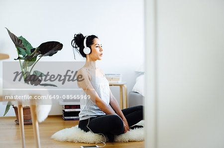 Young woman practicing yoga in living room whilst listening to headphones Stock Photo - Premium Royalty-Free, Image code: 649-08565969