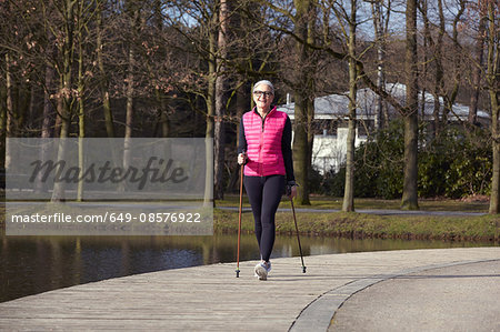 Full length front view of woman nordic walking by pond Stock Photo - Premium Royalty-Free, Image code: 649-08576922