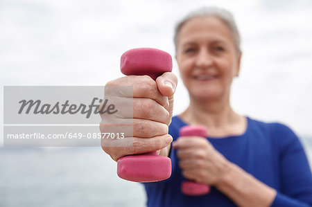 Mature woman exercising with hand weights Stock Photo - Premium Royalty-Free, Image code: 649-08577013