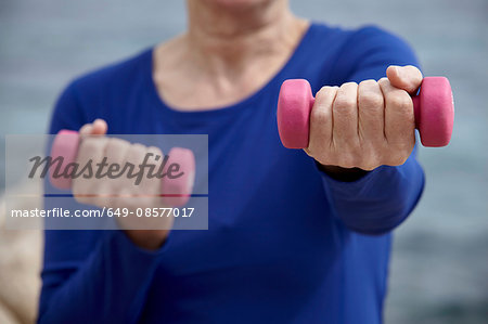 Mature woman outdoors, exercising with hand weights Stock Photo - Premium Royalty-Free, Image code: 649-08577017