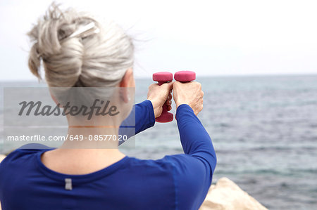 Mature woman beside sea, exercising with hand weights, rear view Stock Photo - Premium Royalty-Free, Image code: 649-08577020