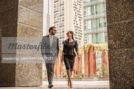 Businessman and woman walking and talking outside office, Dubai, United Arab Emirates Stock Photo - Premium Royalty-Free, Image code: 649-08577527