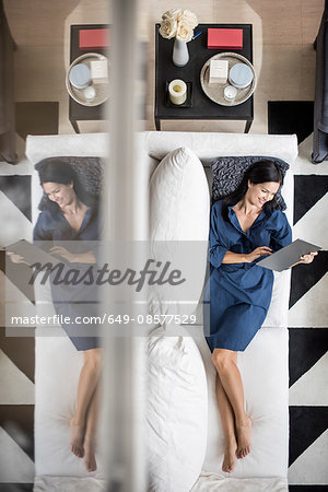 Overhead view of woman lying on hotel room sofa using digital tablet, Dubai, United Arab Emirates Stock Photo - Premium Royalty-Free, Image code: 649-08577529