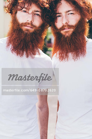 Portrait of young male hipster twins with red beards wearing white tshirts