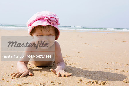 Portrait of female toddler lying on beach, Sagres, Algarve, Portugal Stock Photo - Premium Royalty-Free, Image code: 649-08714144