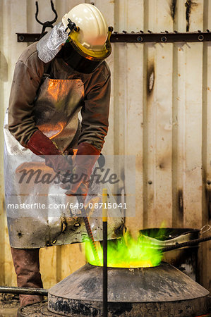 Male foundry worker working with green flamed furnace in bronze foundry