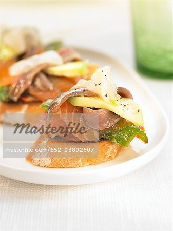 Smoked fish and grilled green peppers on a bite-size slice of bread Stock Photo - Premium Royalty-Free, Image code: 652-03802607