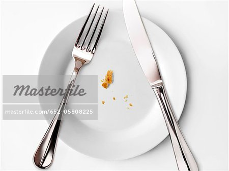 Crumbs on a plate,knife and fork Stock Photo - Premium Royalty-Free, Image code: 652-05808225