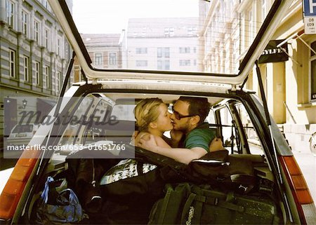 A man and woman kissing in the backseat of a car Stock Photo - Premium Royalty-Free, Image code: 653-01651766