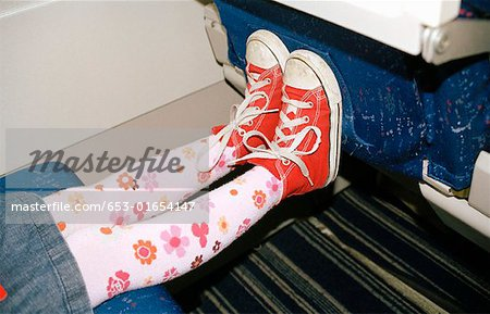Child's feet against airplane seat Stock Photo - Premium Royalty-Free, Image code: 653-01654147