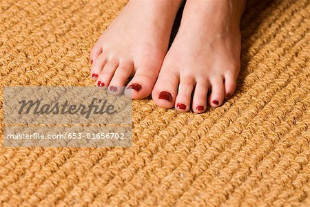 Woman's feet with toenails painted burgundy