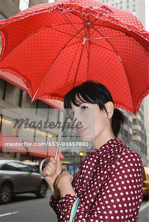 Young woman wearing a polka dot dress and holding a red umbrella in city street, New York City Stock Photo - Premium Royalty-Free, Image code: 653-01657881