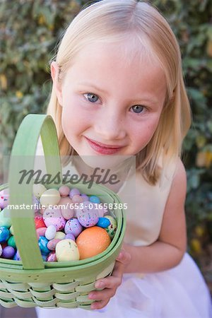 Young girl holding basket full of Easter eggs Stock Photo - Premium Royalty-Free, Image code: 653-01658385