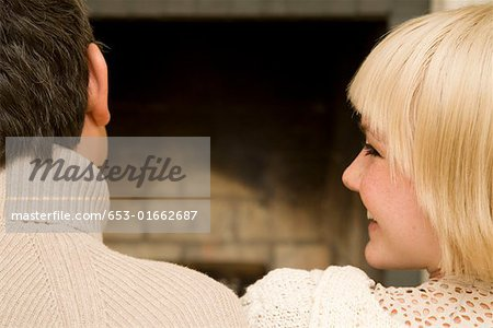 Young couple sitting in front of an open fire together Stock Photo - Premium Royalty-Free, Image code: 653-01662687