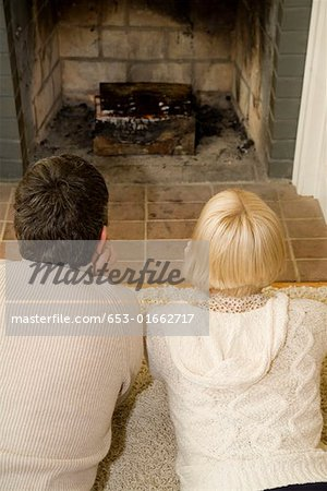 Young couple lying down in front of an open fire together Stock Photo - Premium Royalty-Free, Image code: 653-01662717