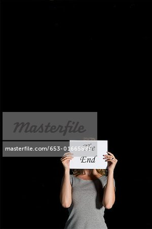 A woman holding a sign for 'The End' Stock Photo - Premium Royalty-Free, Image code: 653-01665885