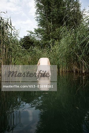 A naked woman resting on the back of a naked man standing in a pond Stock Photo - Premium Royalty-Free, Image code: 653-01698161