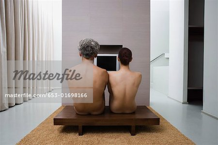 The backs of a naked man and woman sitting Stock Photo - Premium Royalty-Free, Image code: 653-01698166