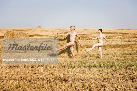 A naked man and woman marching through a field Stock Photo - Premium Royalty-Free, Image code: 653-01698178
