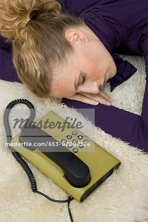 A woman asleep next to a landline phone Stock Photo - Premium Royalty-Free, Image code: 653-02002576