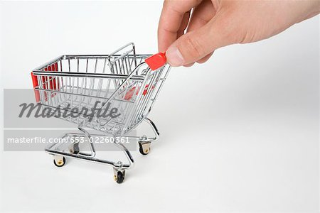 A miniature empty shopping cart being pushed by human fingers Stock Photo - Premium Royalty-Free, Image code: 653-02260361
