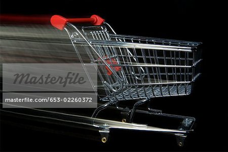 A miniature empty shopping cart moving,blurred motion Stock Photo - Premium Royalty-Free, Image code: 653-02260372