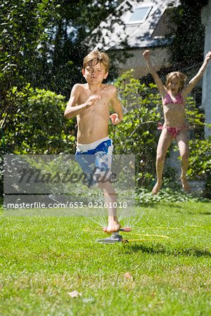 Two children playing in a sprinkler Stock Photo - Premium Royalty-Free, Image code: 653-02261018