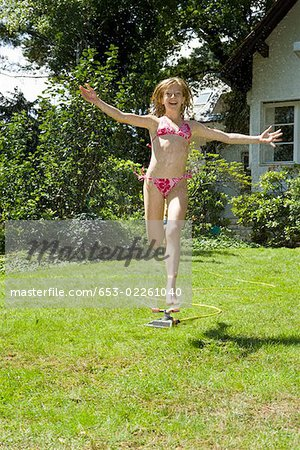 A girl running through a sprinkler Stock Photo - Premium Royalty-Free, Image code: 653-02261040