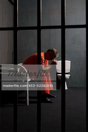 A prisoner sitting on a bed in a prison cell Stock Photo - Premium Royalty-Free, Image code: 653-02261091