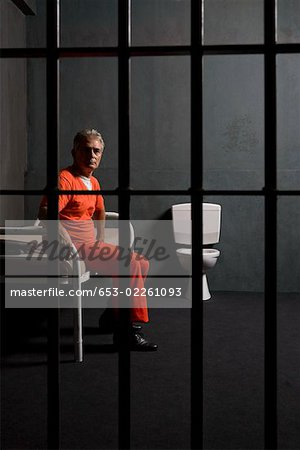 Prisoner sitting on a bed in a prison cell Stock Photo - Premium Royalty-Free, Image code: 653-02261093
