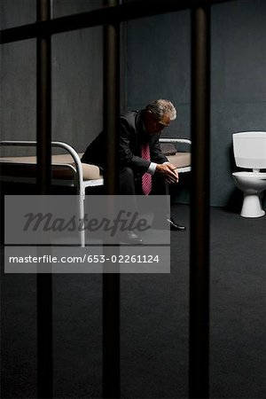 A businessman sitting on a bed in a prison cell Stock Photo - Premium Royalty-Free, Image code: 653-02261124