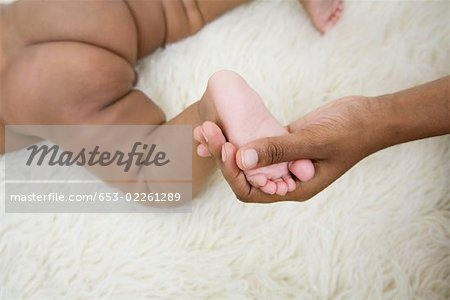 A human hand holding a baby's foot Stock Photo - Premium Royalty-Free, Image code: 653-02261289