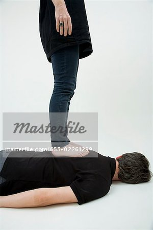 A woman standing on a man's back, obscured faces Stock Photo - Premium Royalty-Free, Image code: 653-02261299