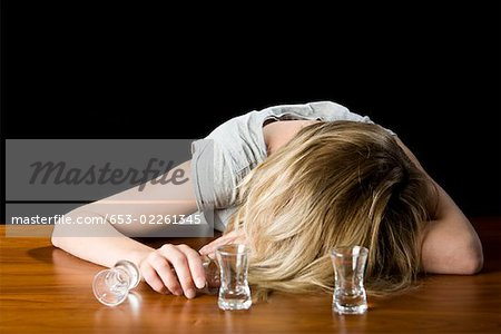 A young woman passed out drunk on a bar counter Stock Photo - Premium Royalty-Free, Image code: 653-02261345