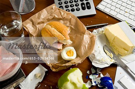 An office desk cluttered with food Stock Photo - Premium Royalty-Free, Image code: 653-02634146
