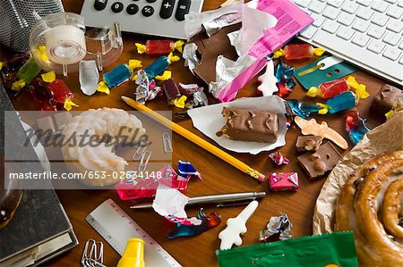 An office desk cluttered with candy and sweets Stock Photo - Premium Royalty-Free, Image code: 653-02634148