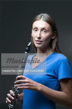 A young woman holding a clarinet Stock Photo - Premium Royalty-Free, Image code: 653-02634492