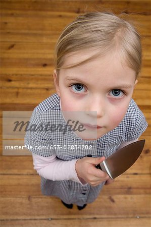 A young girl holding a sharp knife menacingly Stock Photo - Premium Royalty-Free, Image code: 653-02834202