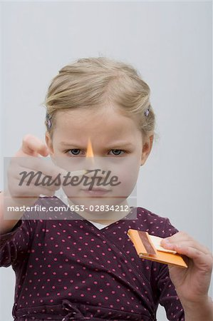 A young girl playing with matches Stock Photo - Premium Royalty-Free, Image code: 653-02834212