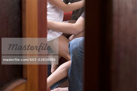 Spying through a crack in the door at a couple sharing an intimate moment Stock Photo - Premium Royalty-Free, Image code: 653-02834490