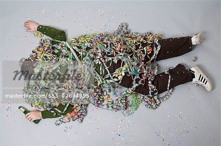 A man passed out and covered in streamers Stock Photo - Premium Royalty-Free, Image code: 653-02834895
