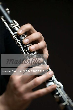 Human hands playing a clarinet Stock Photo - Premium Royalty-Free, Image code: 653-02835395