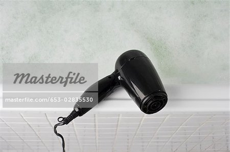 A hair dryer balancing on the edge of a full bathtub Stock Photo - Premium Royalty-Free, Image code: 653-02835530