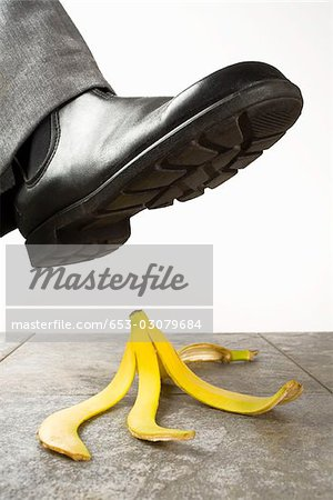 A foot above a banana peel Stock Photo - Premium Royalty-Free, Image code: 653-03079684