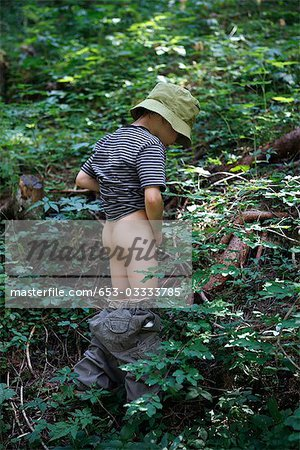 A young boy peeing in the woods Stock Photo - Premium Royalty-Free, Image code: 653-03333785