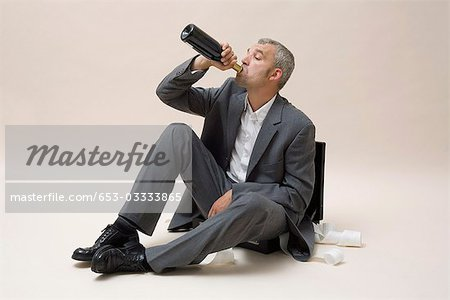 A businessman drinking a bottle of wine Stock Photo - Premium Royalty-Free, Image code: 653-03333865