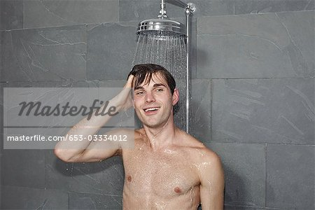 A man standing underneath a shower Stock Photo - Premium Royalty-Free, Image code: 653-03334012
