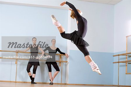 A ballerina leaping through the air as two other women look on Stock Photo - Premium Royalty-Free, Image code: 653-03334174